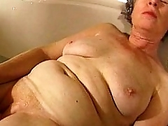 Granny masturbates with a vibrator close by bathtub