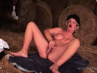 Big titted mature floozy self fucking with giant dildo in all directions a barn